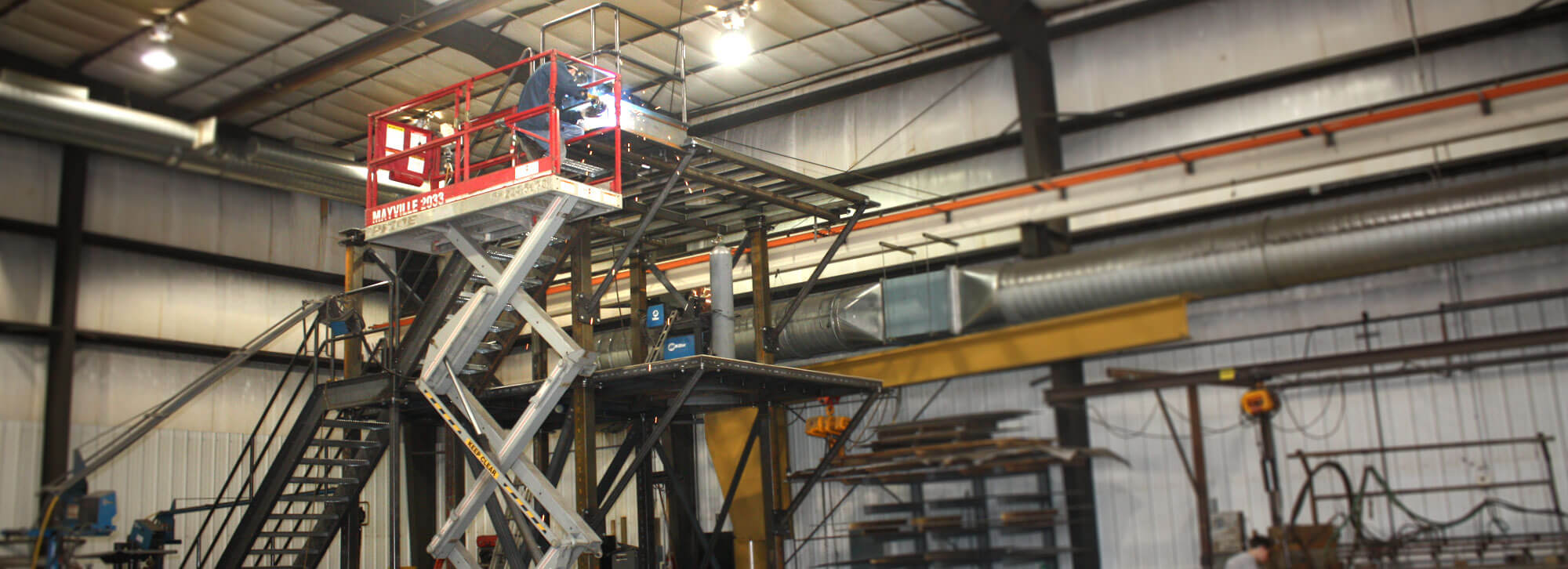 Fabricators at Millwood Metalworks using a scissor lift to weld on a large stair structure
